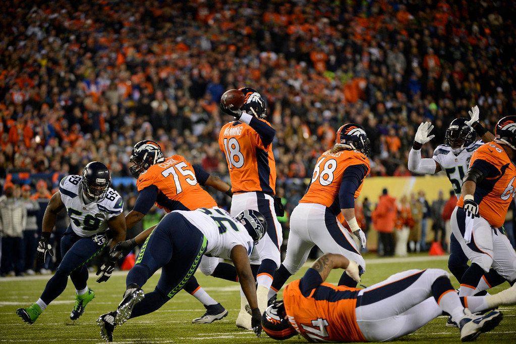 Description of . Denver Broncos quarterback Peyton Manning (18) under pressure during the first quarter. The Denver Broncos vs the Seattle Seahawks in Super Bowl XLVIII at MetLife Stadium in East Rutherford, New Jersey Sunday, February 2, 2014. (Photo by Joe Amon/The Denver Post)