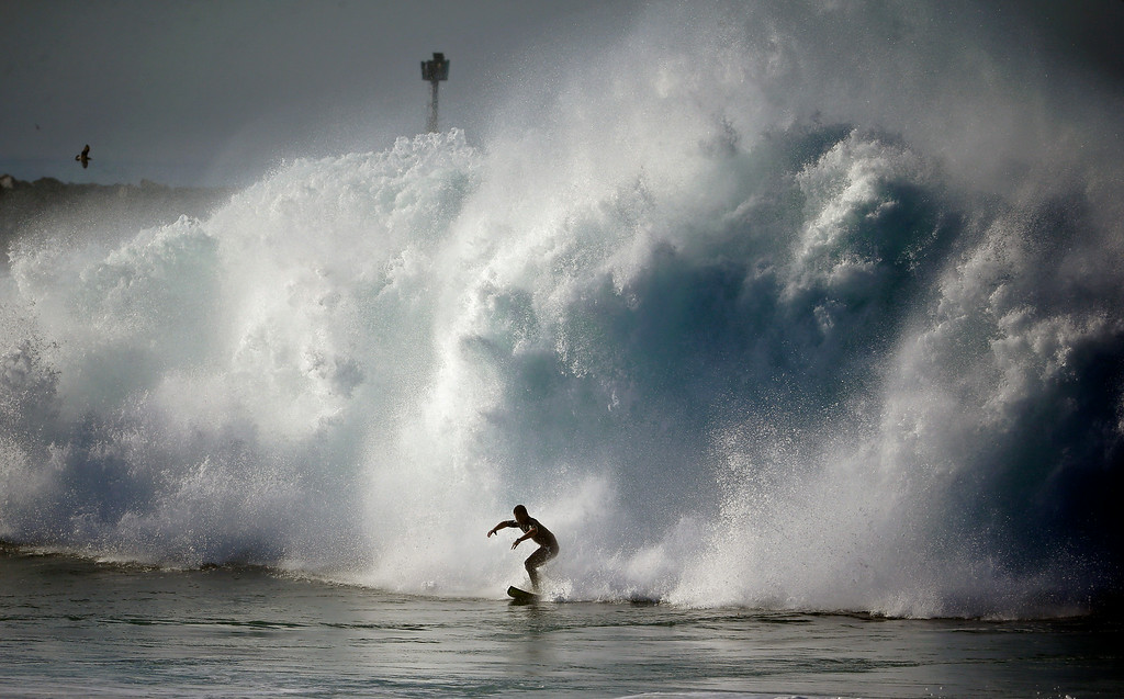 Description of . A surfer rides a wave at the wedge in Newport Beach, Calif., Wednesday, Aug. 27, 2014. Southern California beachgoers experienced much higher than normal surf, brought on by Hurricane Marie spinning off the coast of Mexico. (AP Photo/Chris Carlson)