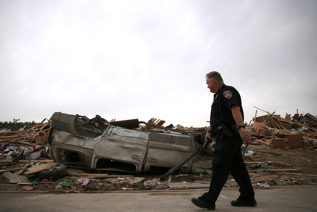 Description of . A police officer walks past an overturned car at a homesite that was destroyed by a tornado on Sunday, April 29, 2014 in Vilonia, Arkansas.  (Photo by Mark Wilson/Getty Images)