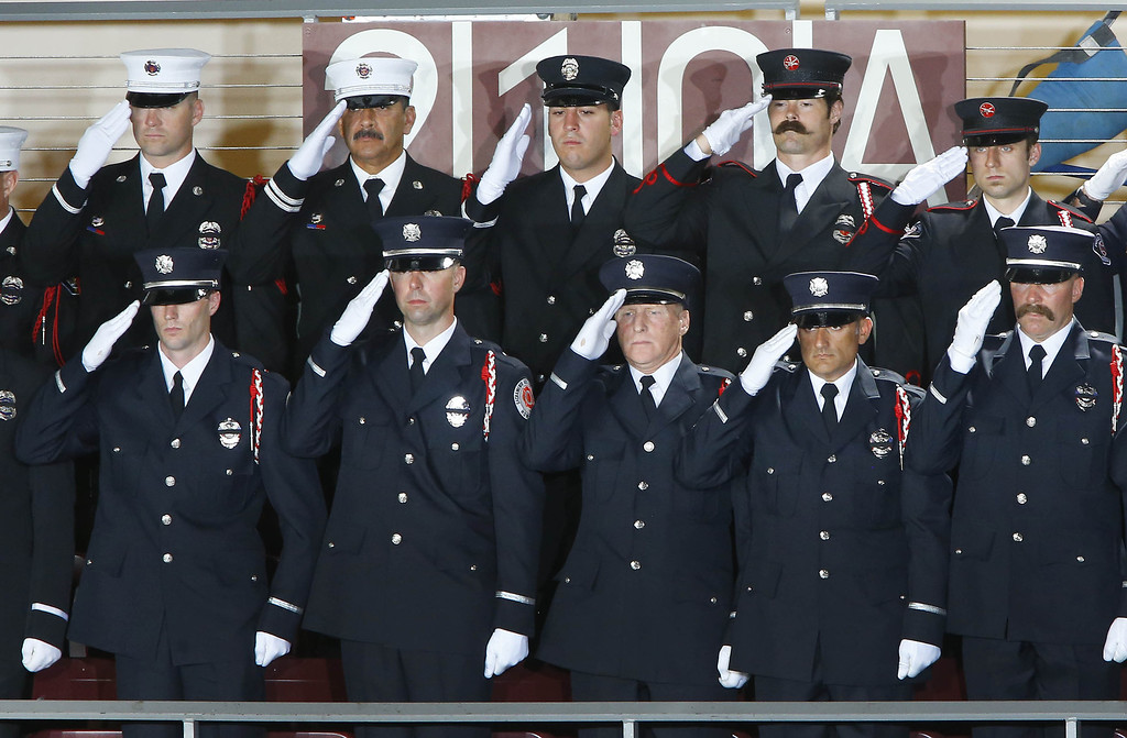 Description of . Firefighters from Sacramento stand during the national anthem during a memorial service honoring 19 fallen firefighters at Tim's Toyota Center July 9, 2013 in Prescott Valley, Arizona.  (Photo by David Kadlubowski-Pool/Getty Images)