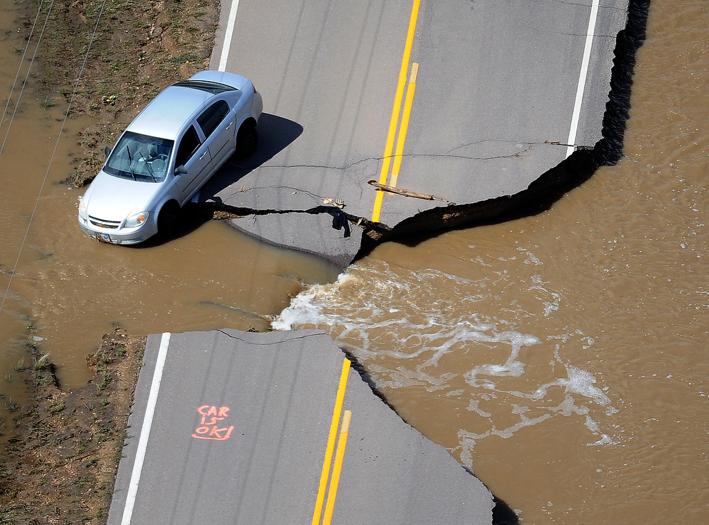 Description of . A car sits partly off the washed-out road near Longmont on Monday, September 16, 2013.   (Photo By Tim Rasmussen/The Denver Post)