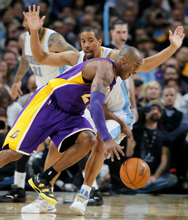 Description of . Los Angeles Lakers guard Kobe Bryant, front, pursues a loose ball as Denver Nuggets guard Andre Miller  defends in the third quarter of the Nuggets' 119-108 victory in an NBA basketball game in Denver on Monday, Feb. 25, 2013. (AP Photo/David Zalubowski)