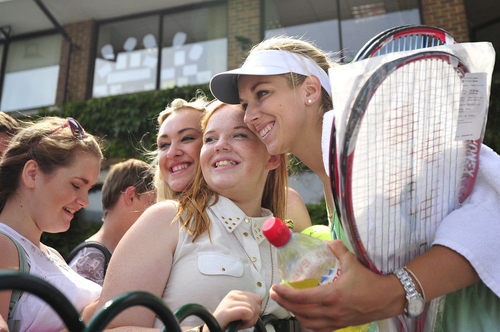 Description of . Germany\'s Sabine Lisicki poses with fans after training on day eleven of the 2013 Wimbledon Championships tennis tournament at the All England Club in Wimbledon, southwest London, on July 5, 2013, ahead of her women\'s singles final match on July 6. GLYN KIRK/AFP/Getty Images