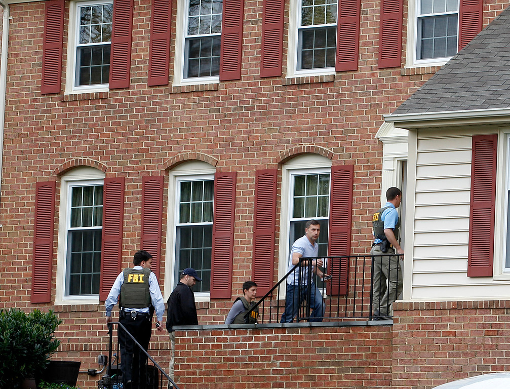 Description of . FBI agents escort Ruslan Tsarni, uncle of the Boston Marathon bombing suspects, second from right, into his home in Montgomery Village in Md. Friday, April, 19, 2013. The brothers, who came from a Russian region near Chechnya, lived together on Norfolk Street in Cambridge, Mass. They had been in the country for about a decade, according to an uncle, Ruslan Tsarni of Montgomery Village, Md. (AP Photo/Jose Luis Magana)