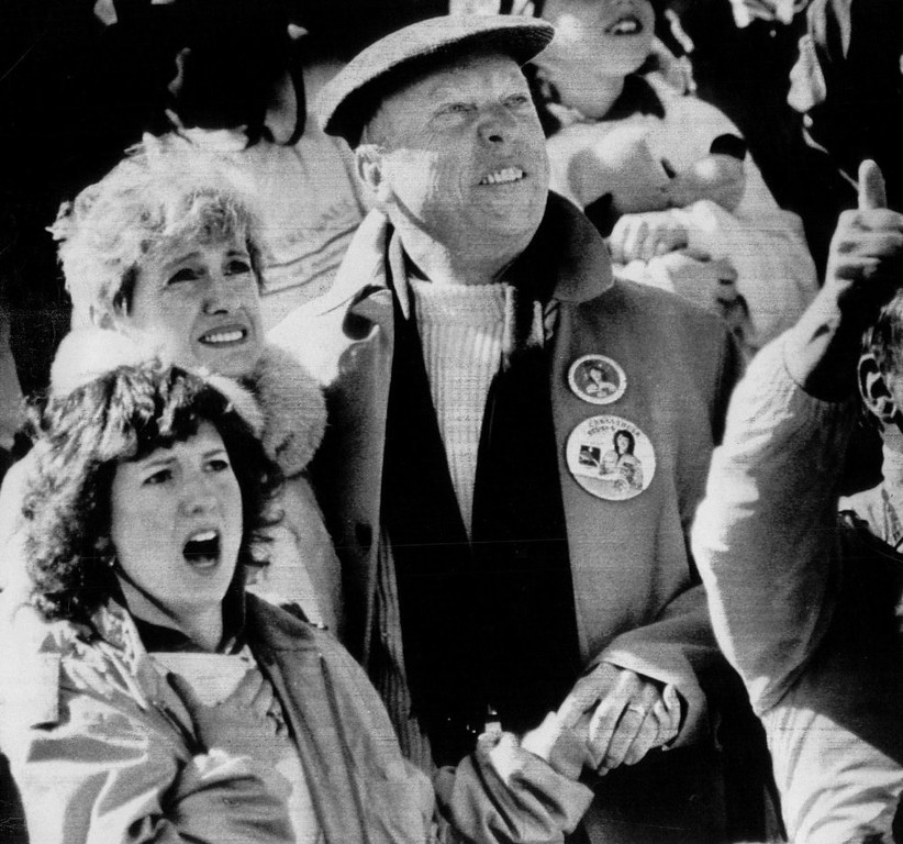 Description of . The parents of teacher astronaut Christa McAuliffe, Edward and Grace Corrigan hold hands as they watch the launch of space shuttle Challenger on Jan. 28, 1986 at the Kennedy Space Center VIP area. Christa\'s sister Lisa Bristol (L) has her mouth agape as the orbiter lifts off. Denver Post Library Archive