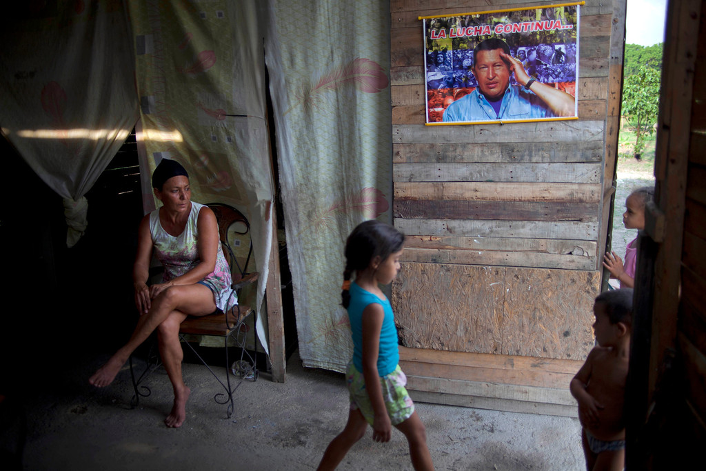 Description of . In this April 8, 2013 photo, Yadaira Nunez, 43, sits in her wooden shack next to a poster of Venezuela's late President Hugo Chavez that reads in Spanish;