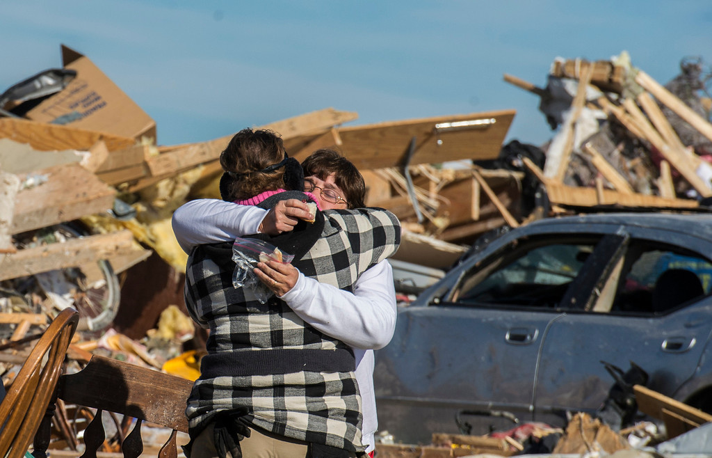 Description of . Kim Bendixen, facing, is embraced by a friend as the toll of the day wears on as homeowners dig out what they can in Washington, Ill., Tuesday, Nov. 19, 2013, after more than 1,000 homes were devastated by a F4 tornado that passed through Sunday. Kim said that her father was rescued out of the rubble, and was doing better. The twister was the most powerful to hit Illinois since 1885 with wind speeds greater than 200 mph. (AP Photo/Journal Star, Fred Zwicky)