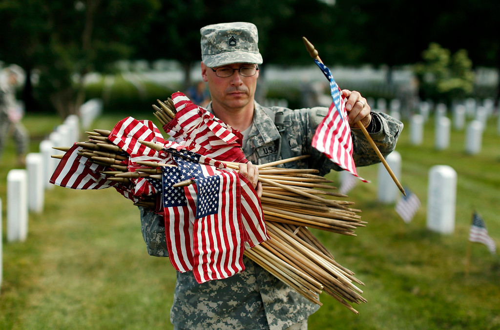 Description of . A soldier from the Third U.S. Infantry Regiment (The Old Guard) carries flags to be placed beside graves at Arlington National Cemetery in Virginia May 23, 2013. REUTERS/Kevin Lamarque