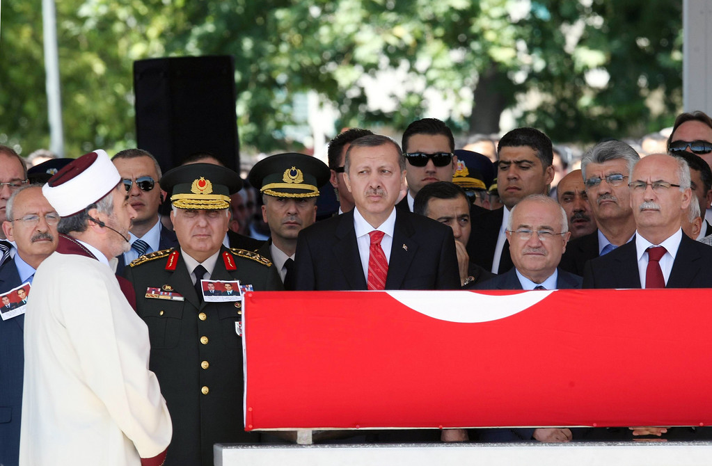 Description of . Turkey's Prime Minister Recep Tayyip Erdogan, center left, Parliament Speaker Cemil Cicek, center right, Chief of Staff Gen. Necdet Ozel, third left, and other officials attend a religious funeral for Captain Gokhan Ertan, at a mosque in the eastern Turkish city of Malatya, Turkey, Friday, July 6, 2012. Turkey's Prime Minister Recep Tayyip Erdogan and top military commanders have joined hundreds of mourners at the funeral of two pilots whose jet was shot down by Syria two weeks ago. The somber ceremony took place at an air base in Malatya, from where the pilots' plane had originally taken off. (AP Photo)