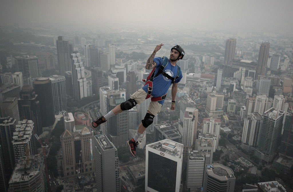 Description of . Base jumper Theo Gagliardini from France leaps from the 300-meters Open Deck of the Malaysia's landmark Kuala Lumpur Tower during the International Tower Jump in Kuala Lumpur on September 27, 2013. AFP PHOTO / MOHD RASFAN/AFP/Getty Images