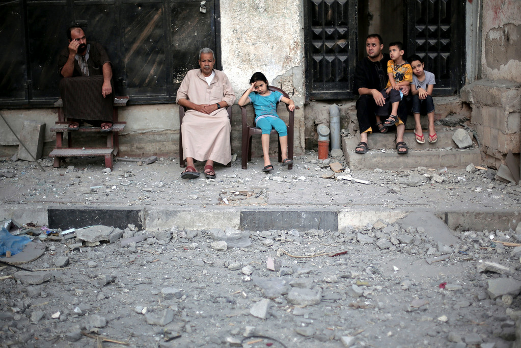 Description of . Neighbors of Palestinian Hamas leader, Mahmoud Zahar, sit outside their homes following an early morning Israeli missile strike that destroyed Zahar's house in Gaza City, Wednesday, July 16, 2014. Israel on Wednesday intensified air attacks on Hamas targets in the Gaza Strip following a failed Egyptian cease-fire effort, targeting the homes of four senior leaders of the Islamic militant movement and ordering tens of thousands of residents to evacuate border areas. (AP Photo/Khalil Hamra)