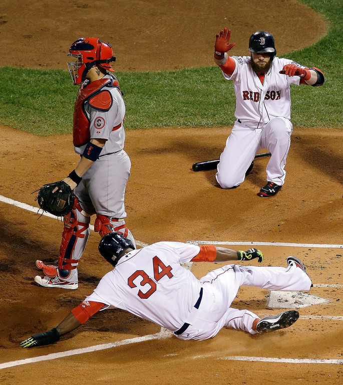 Description of . Boston Red Sox designated hitter David Ortiz slides into home as Jonny Gomes, right, watches during the first inning of Game 1 of baseball's World Series Wednesday, Oct. 23, 2013, in Boston. St. Louis Cardinals catcher Yadier Molina is at left. (AP Photo/Matt Slocum)