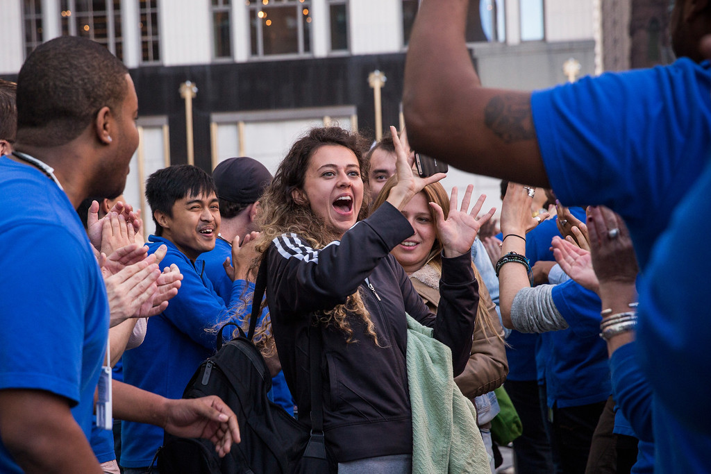 Description of . Customers are greeted by Apple employees while entiring the Fifth Avenue Apple Store to buy an iPhone 5S on September 20, 2013 in New York City.  (Photo by Andrew Burton/Getty Images)