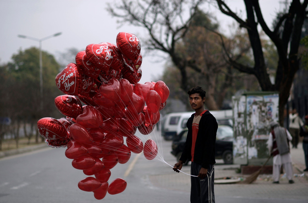 Description of . A Pakistani man stands on a roadside waiting for customers to sell heart-shaped balloons on Valentine's Day, in Islamabad, Pakistan, Thursday, Feb. 14, 2013. Romance may not be dead in Pakistan but it is under attack. Conservatives in Pakistan are attacking the romantic holiday as a western-inspired event helping to spread vulgarity in their country and putting up posters calling on people to boycott the holiday. But romantics are fighting back with an arsenal of flowers, pink teddy bears and heart-shaped balloons. (AP Photo/Muhammed Muheisen)