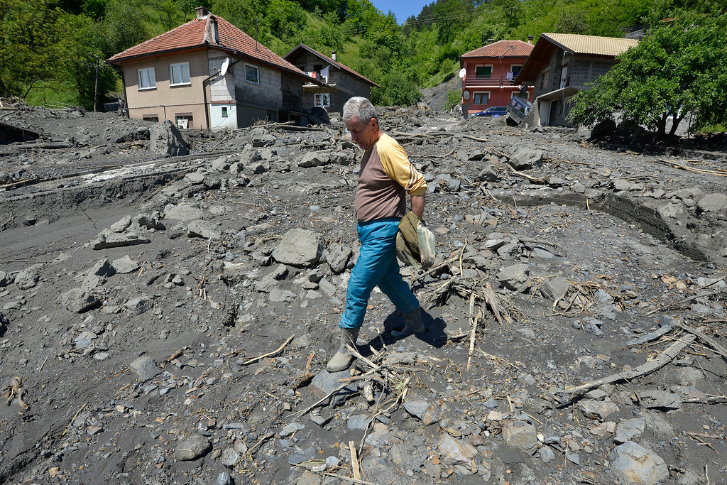 Description of . Ramiz Skopljak, 65, walks where his house once stood and was swept by the river last week in the village of Topcic Polje, near the Bosnian town of Zenica, 90 kilometers north of Sarajevo, on Monday May 19, 2014. (AP Photo/Sulejman Omerbasic)