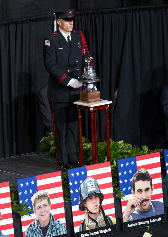 Description of . A bell is rung for each fallen firefighter during a memorial service for the 19 fallen firefighters at Tim's Toyota Center in Prescott Valley, Ariz. on Tuesday, July 9, 2013.   (AP Photo/The Arizona Republic, Michael Chow, Pool)