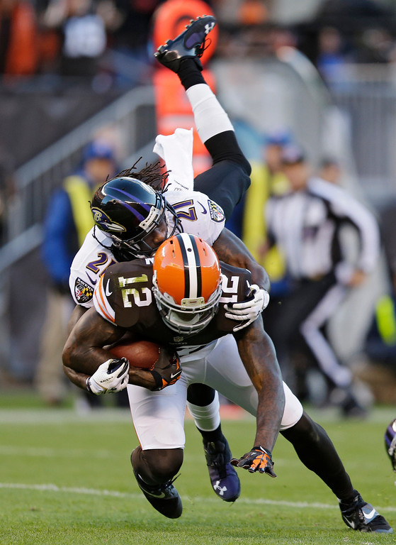 . Baltimore Ravens cornerback Lardarius Webb (21) tackles Cleveland Browns wide receiver Josh Gordon (12) after a first quarter pass catch in an NFL football game Sunday, Nov. 3, 2013, in Cleveland. (AP Photo/Tony Dejak)