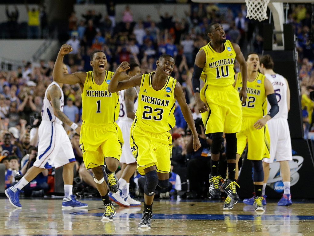 Description of . Michigan celebrates after beating Kansas  87-85 in overtime of a regional semifinal game in the NCAA college basketball tournament, Friday, March 29, 2013, in Arlington, Texas. (AP Photo/David J. Phillip)