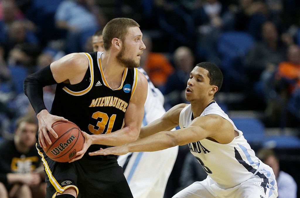Description of . Milwaukee's Matt Tiby (31) protects the ball from Villanova's Josh Hart during the second half of a second-round game in the NCAA college basketball tournament in Buffalo, N.Y., Thursday, March 20, 2014. (AP Photo/Frank Franklin II)