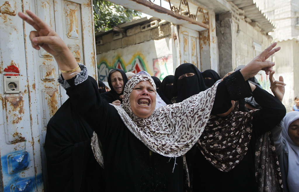 Description of . Relatives mourn during the funeral of Bashir Abdel Aal, a 20-year-old Hamas militant who was killed by Israeli tank shells minutes before a five-hour truce went into effect, on July 17, 2014 in the southern Gaza Strip town of Rafah. An Israeli official said the Jewish state had agreed a ceasefire with Hamas that will begin at 0300 GMT on July 18, but the Islamist movement refused to confirm the deal. AFP PHOTO / SAID KHATIB/AFP/Getty Images