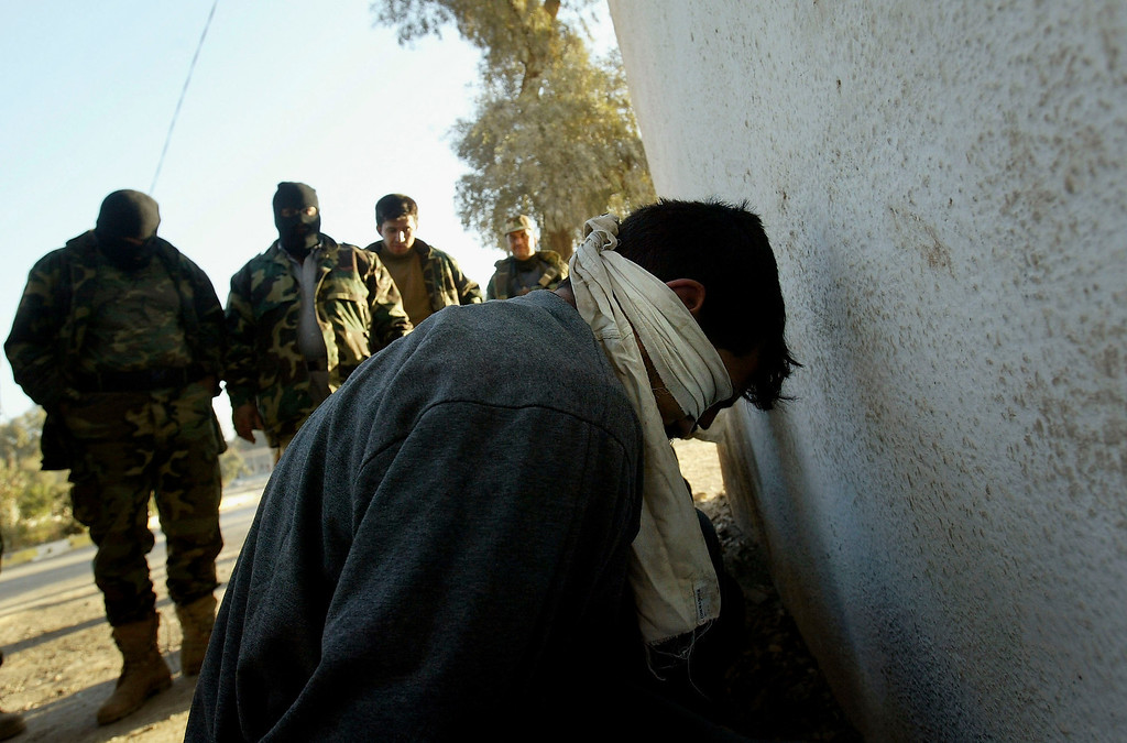 . An suspected Iraqi insurgent is detained by commandos of the 3rd battalion of the Commandos brigade after raids against suspected insurgents, 30km north of Baghdad, on February 18, 2005 In Taji, Iraq. Most of the members of the Commandos Elite Force were members of the security apparatus under the former regime. (Photo by Ghaith Abdul-Ahad/Getty Images).
