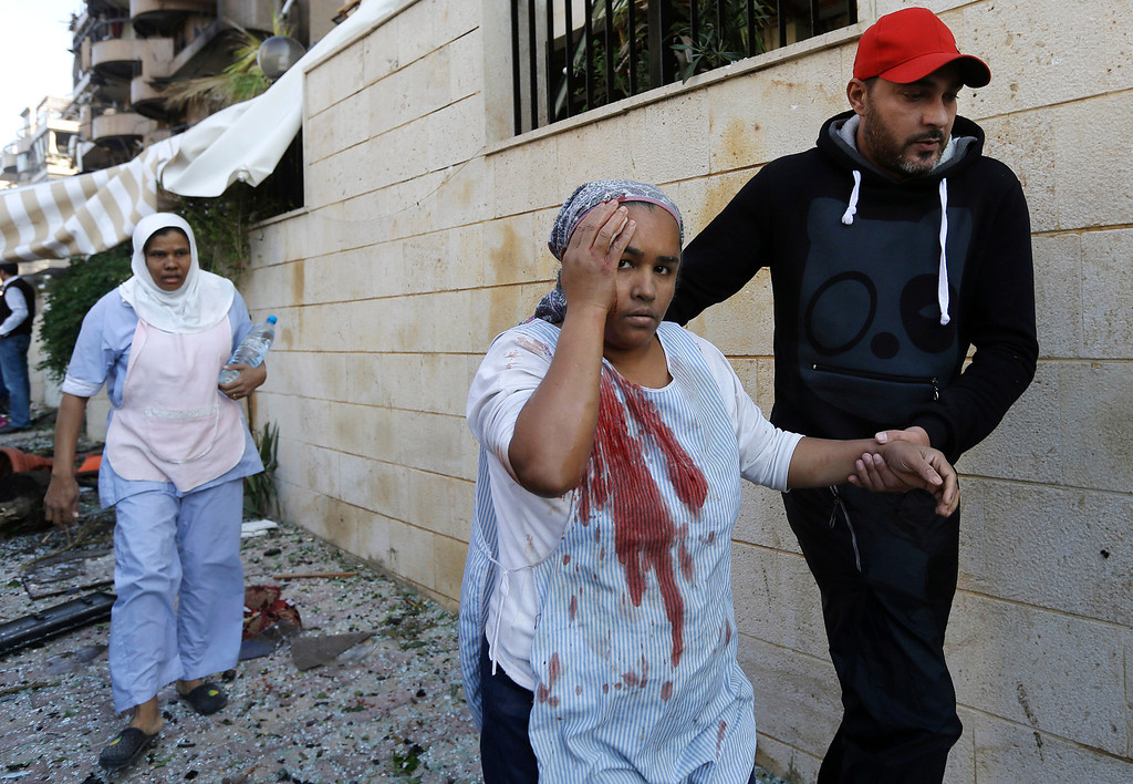 Description of . A Lebanese man helps an injured domestic worker, at the scene where two explosions have struck near the Iranian Embassy killing many, in Beirut, Lebanon, Tuesday Nov. 19, 2013. The blasts in south Beirut\'s neighborhood of Janah also caused extensive damage on the nearby buildings and the Iranian mission. The area is a stronghold of the militant Hezbollah group, which is a main ally of Syrian President Bashar Assad in the civil war next door. It\'s not clear if the blasts are related to Syria\'s civil war. (AP Photo/Hussein Malla)