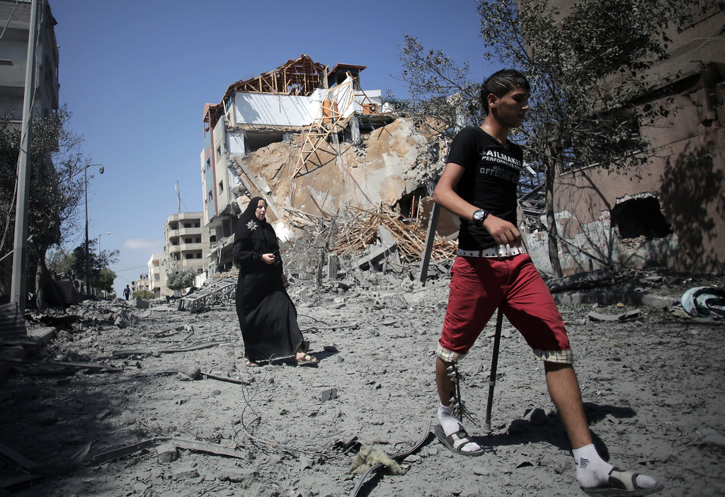 Description of . Palestinians walk past the Hamas movement's Al-Aqsa satellite TV station which was hit by an Israeli strike in Gaza City, Thursday, July 31, 2014. (AP Photo/Khalil Hamra)
