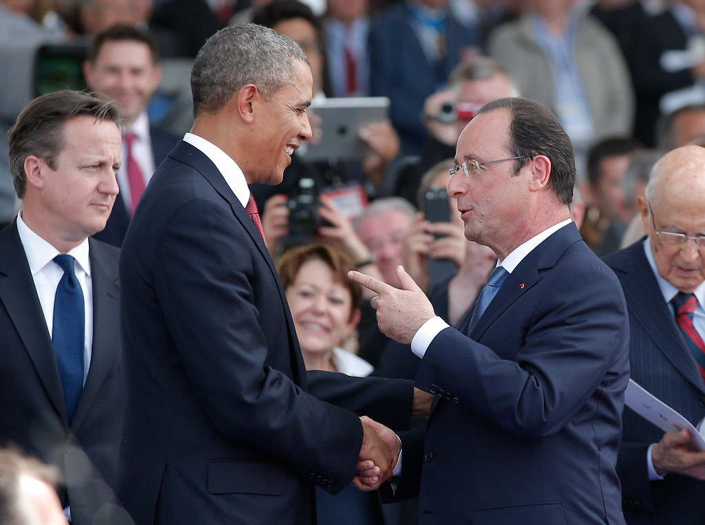 Description of . French President Francois Hollande, right, speaks with U.S. President Barack Obama as British Prime Minister David Cameron, left, looks on during the D-Day commemoration at the Ouistreham beach, western France, Friday, June 6, 2014.  (AP Photo/Christophe Ena, Pool)