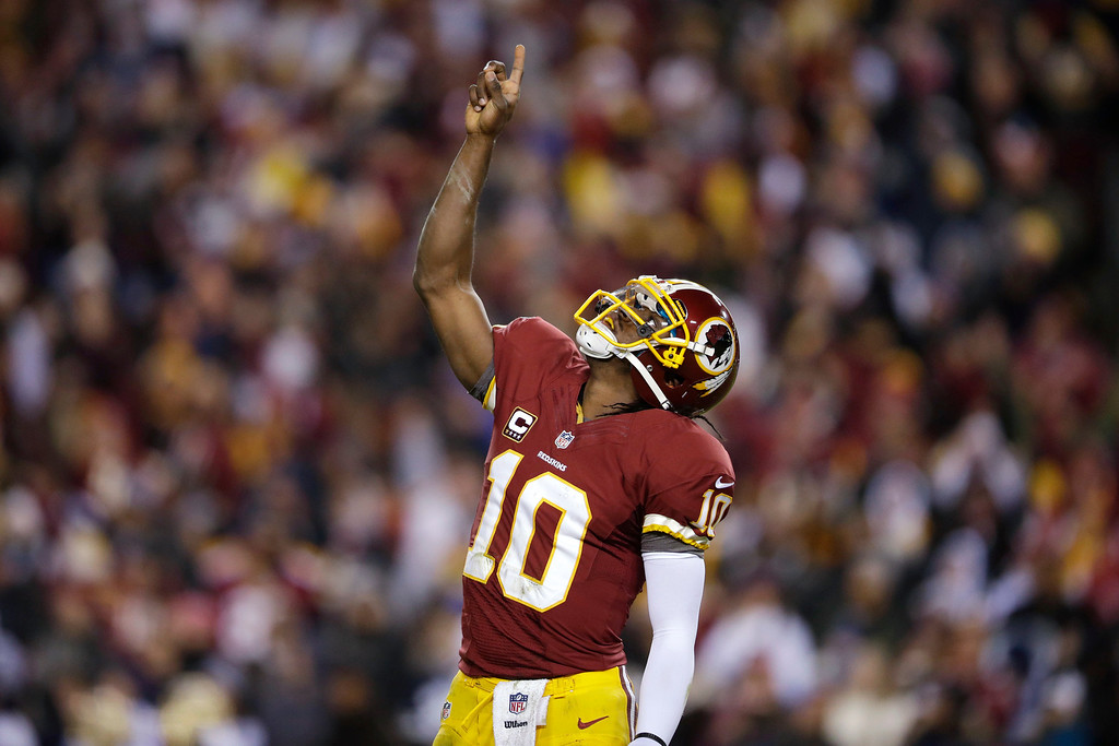 . Washington Redskins quarterback Robert Griffin III celebrates a touchdown during the first half of an NFL football game against the Dallas Cowboys on Sunday, Dec. 30, 2012, in Landover, Md. (AP Photo/Evan Vucci)