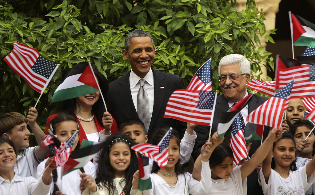 Description of . U.S. President Barack Obama (C) poses with Palestinian kids during a visit to the Church of the Nativity with Palestinian President Mahmoud Abbas (R) on March 22, 2013 in Bethlehem, West Bank. (Photo by Atef Safadi-Pool/Getty images)