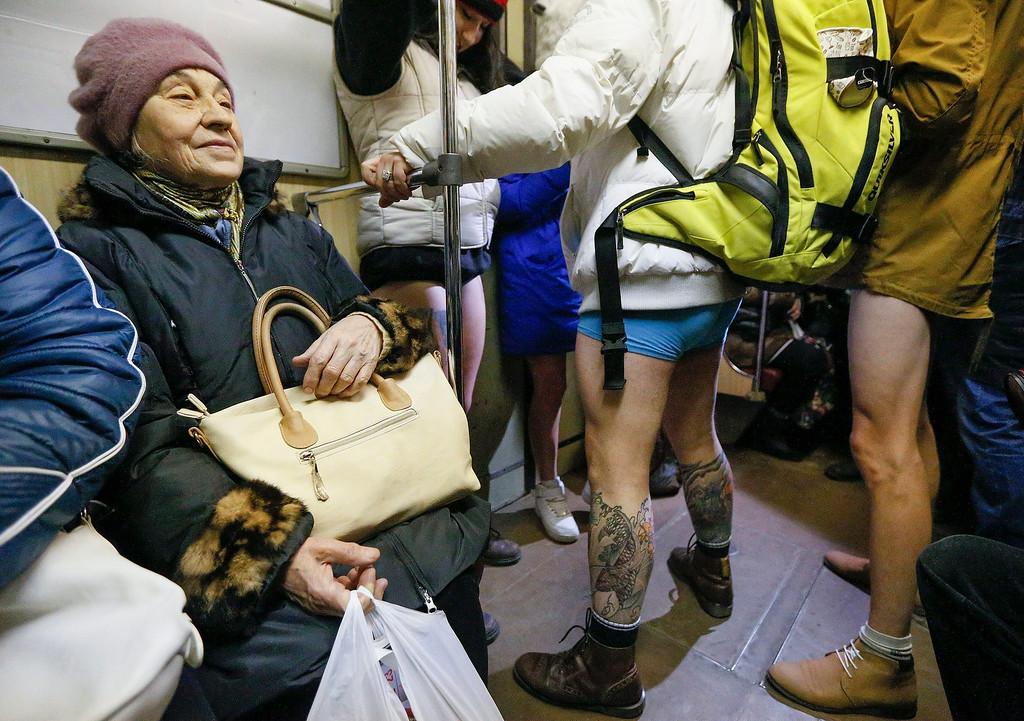 Description of . An elderly woman looks on young Ukrainians wearing no pants as they participate in the first 'No Pants Subway Ride' in Kiev, Ukraine, 12 January 2014. No Pants Subway Ride is an annual global event started in New York, USA in 2002. This is the first time that the event is organized in Ukraine.  EPA/SERGEY DOLZHENKO