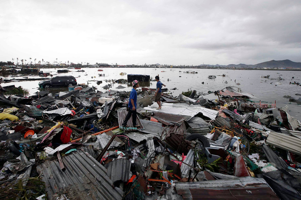 Description of . Boys stand on debris from damaged houses in Tacloban city, Leyte province, central Philippines on Sunday, Nov. 10, 2013. The city remains littered with debris from damaged homes as many complain of shortages of food and water and no electricity since Typhoon Haiyan slammed into their province. Haiyan, one of the most powerful storms on record, slammed into six central Philippine islands on Friday, leaving a wide swath of destruction and scores of people dead. (AP Photo/Bullit Marquez)