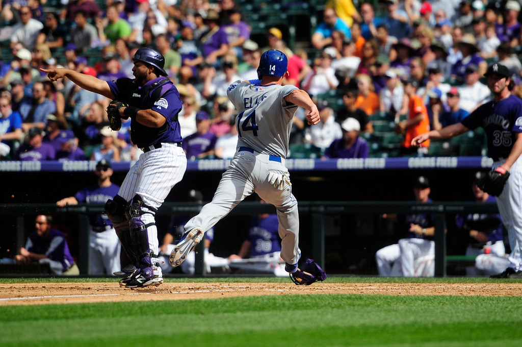 Description of . Mark Ellis (14) of the Los Angeles Dodgers stretches to cross home before the third out of the inning as Wilin Rosario (20) of the Colorado Rockies indicates the out beat the score during the action in Denver on Monday, September 2, 2013. The Colorado Rockies hosted the Los Angeles Dodgers at Coors Field.   (Photo by AAron Ontiveroz/The Denver Post)