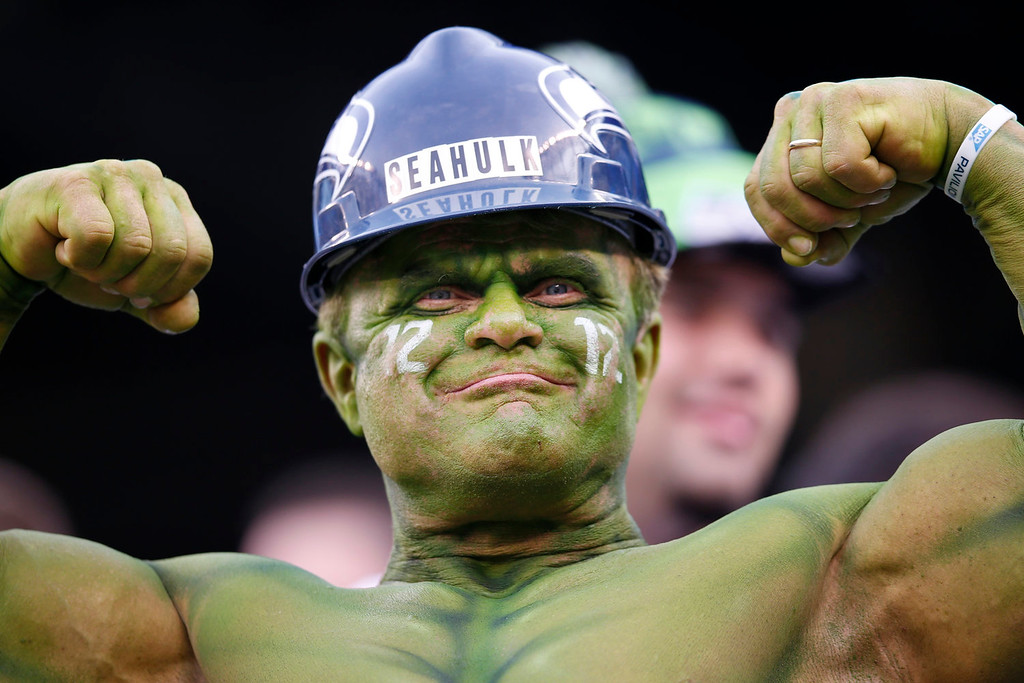 Description of . A Seattle Seahawks fan flexes at MetLife Stadium before the NFL Super Bowl XLVIII football game between the Seattle Seahawks and the Denver Broncos Sunday, Feb. 2, 2014, in East Rutherford, N.J. (AP Photo/Evan Vucci)