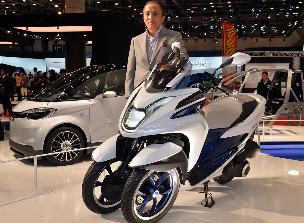 Description of . Japan's motorcycle giant Yamaha Motor president Hiroyuki Yanagi displays the prototype model of a trike