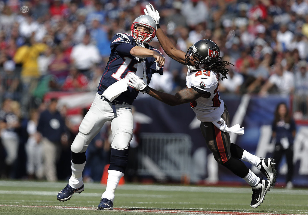 Description of . Quarterback Tom Brady #12 of the New England Patriots gets off a pass as Mark Barron #23 of the Tampa Bay Buccaneers flies into him during the first half at Gillette Stadium on September 22, 2013 in Foxboro, Massachusetts.  (Photo by Winslow Townson/Getty Images)