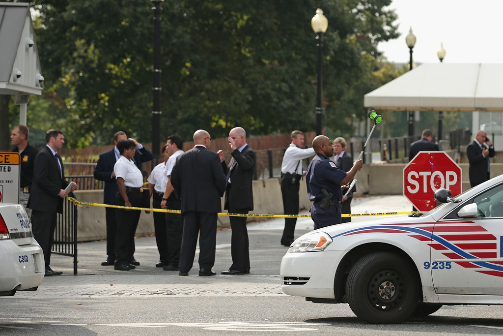 Description of . U.S. Secret Service Uniform Division officers and Metropolitan Police Department officers investigate a vehicle security barrier outside the White House October 3, 2013 in Washington, DC. Two people were injured after a car chase began at this barrier and ended near the U.S. Capitol with gun shots fired.  (Photo by Chip Somodevilla/Getty Images)