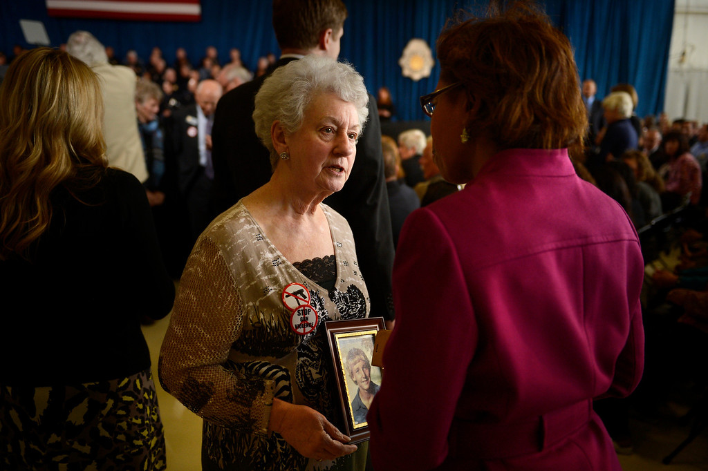 Description of . DENVER, CO. - APRIL 03: Carole Bell of Centennial talking to Colorado State Rep Rhonda Fields while carrying photograph of her son Christopher who was accidentally killed by a rifle shot when he was 14 in the early 80's. An unaccompanied 15 year old boy was hunting rabbits on a golf course when he hit Christopher. President Barack Obama is about to speak to uniformed officers and community leaders at the Denver Police Academy calling for Congress to act more like the state's Democratic-controlled legislature to pass stronger gun-control laws. (Photo By Joe Amon/The Denver Post)