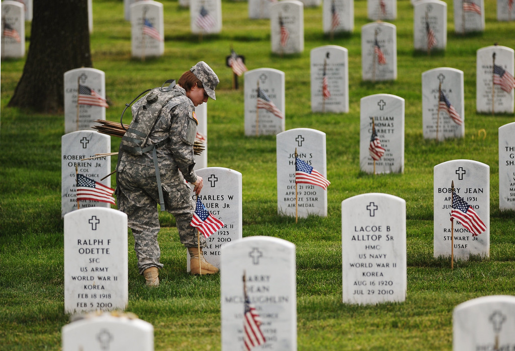 Description of . Staff Sergeant Karrin Kampa (L) of the Third US Infantry Regiment, The Old Guard, place flags in front of graves at Arlington National Cemetery on May 23, 2013 in Arlington, Virginia ahead of Memorial Day.  AFP PHOTO/Mandel NGAN/AFP/Getty Images