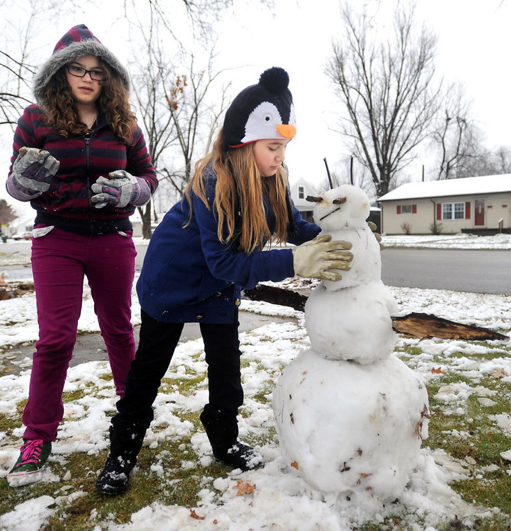 Description of . Ilandra Whittaker, 9, right, uses a rock to add one of three buttons on the snowman she and her sister Ivellana Whittaker, 12, were building in the front yard of their Owensboro, Ky. home Wednesday afternoon, Dec. 26, 2012. The Whittaker sisters said they were enjoying their break from the classroom and enjoying the snow, although they had both hoped for more snow as was predicted. (AP Photo/The Messenger-Inquirer, Jenny Sevcik)