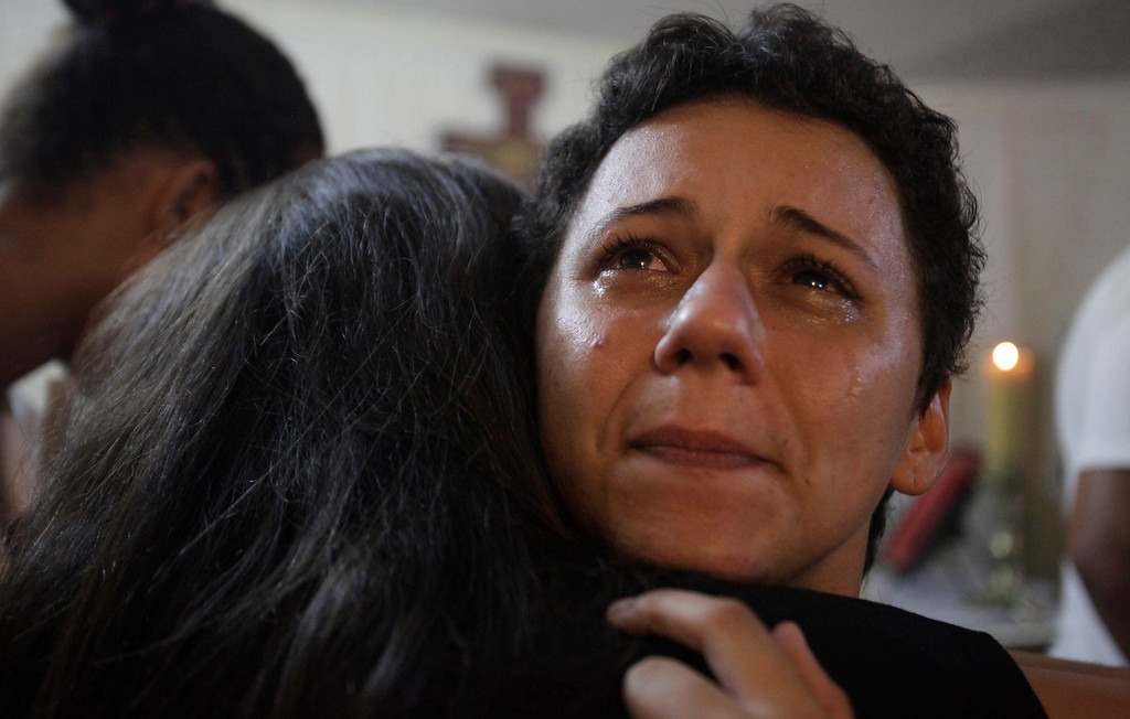 Description of . Lidiane Pereira (R) reacts after she receives her habit upon reaching the level of