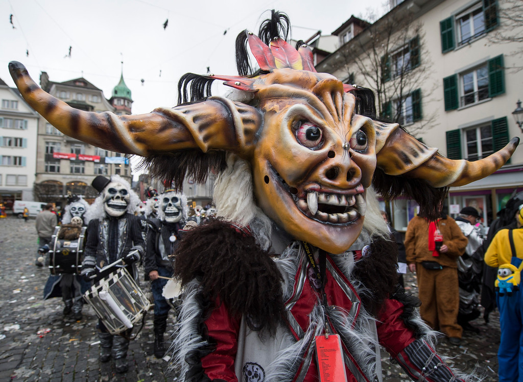 Description of . Revelers in carnival costumes attend the opening of the Lucerne carnival in Lucerne, Switzerland, on the so-called dirty Thursday, Feb. 27, 2014. (AP Photo/Keystone, Sigi Tischler)