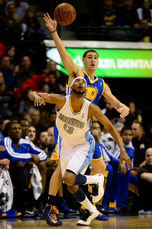 Description of . Denver Nuggets small forward Corey Brewer (13) steals the ball from Golden State Warriors shooting guard Klay Thompson (11) during the first half at the Pepsi Center on Sunday, January 13, 2013. AAron Ontiveroz, The Denver Post