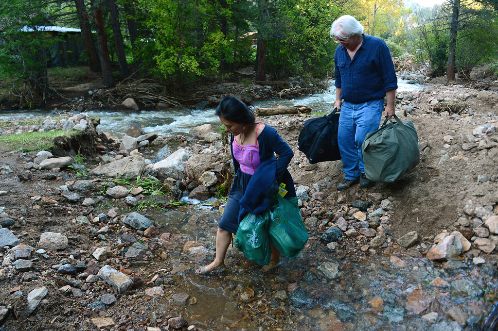 Description of . LEFTHAND CANYON, CO - SEPTEMBER 19: Lefthand Canyon residents Scott Peoples, right, and his wife Hyung Joo Kim ford a small stream along a path next to Lefthand Creek in Lefthand Canyon Drive west of Boulder, Co on September 19, 2013 . The couple, after having stayed four days during the floods, then getting evacuated by helicopter, decided they wanted to move back into their home. Despite the fact that they are cut off on both ends of the canyon as the roads are destroyed, they would rather be at home than in a hotel or with friends. They have cars on both ends of the destroyed bridges and are able to get home as well as get to town and to work. They have a generator for electricity and their home phone works but they don't have running water. (Photo By Helen H. Richardson/ The Denver Post)