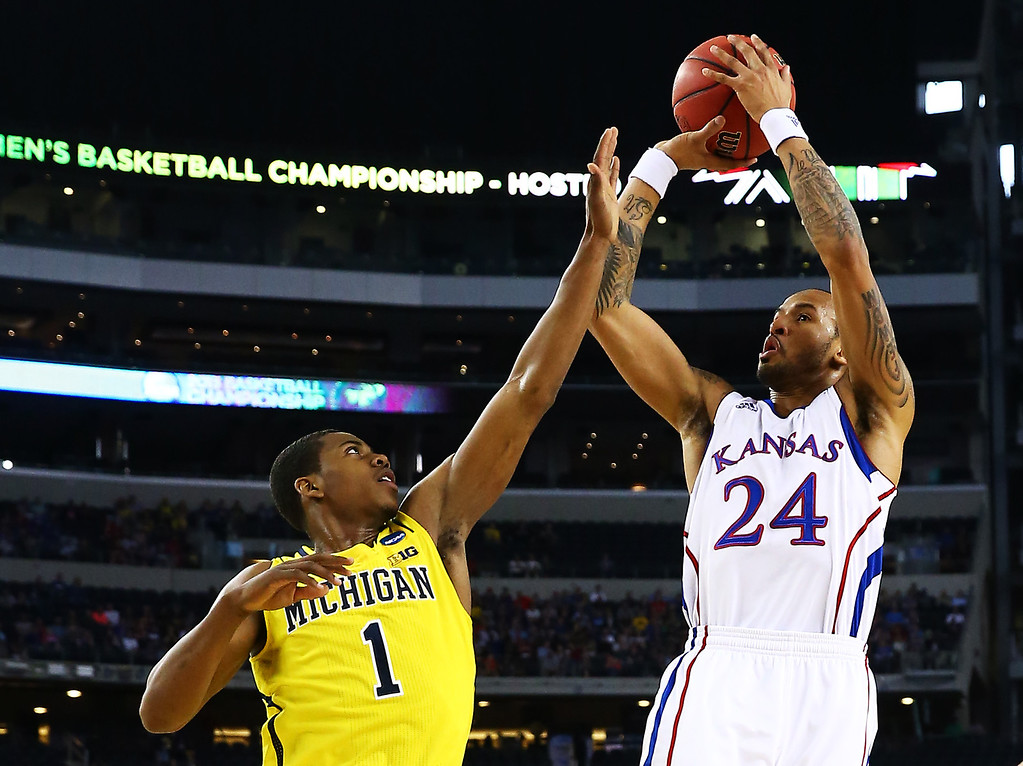 Description of . ARLINGTON, TX - MARCH 29:  Travis Releford #24 of the Kansas Jayhawks shoots over Glenn Robinson III #1 of the Michigan Wolverines in the first half during the South Regional Semifinal round of the 2013 NCAA Men\'s Basketball Tournament at Dallas Cowboys Stadium on March 29, 2013 in Arlington, Texas.  (Photo by Tom Pennington/Getty Images)