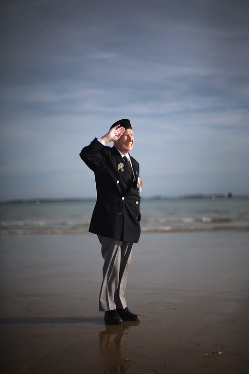 Description of . D-Day veteran Bill Price, aged 99, who celebrates his 100th birthday on July 24, poses on Gold Beach for well wishers after the last ever flag raising ceremony by the Surrey Normandy Veterans Association on June 6, 2014 in Arromanches Les Bains, France.   (Photo by Christopher Furlong/Getty Images)