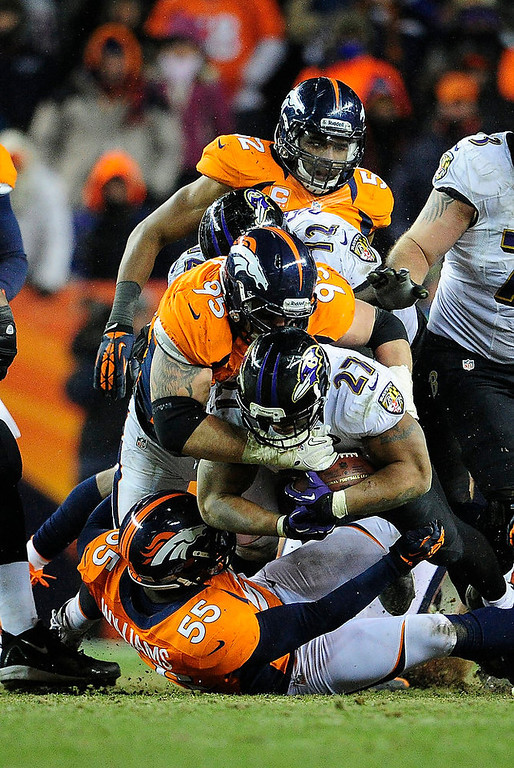 . Denver Broncos defensive end Derek Wolfe (95) tackles Baltimore Ravens running back Ray Rice (27) in overtime. The Denver Broncos vs Baltimore Ravens AFC Divisional playoff game at Sports Authority Field Saturday January 12, 2013. (Photo by AAron  Ontiveroz,/The Denver Post)