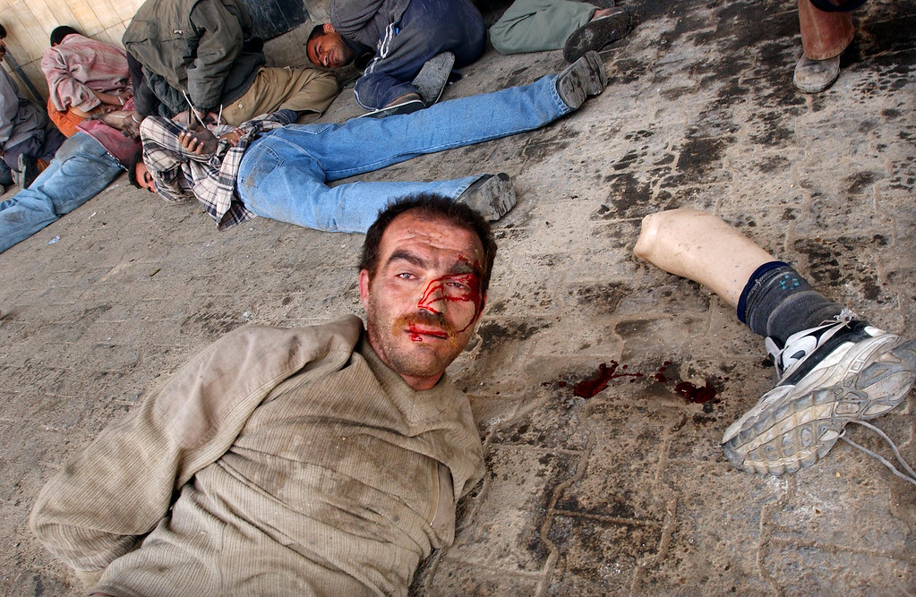Description of . A man lies handcuffed with his artificial leg near his head after U.S. Marines caught him and other looters robbing from a bank April 16, 2003 in Baghdad, Iraq. (Photo by Spencer Platt/Getty Images)