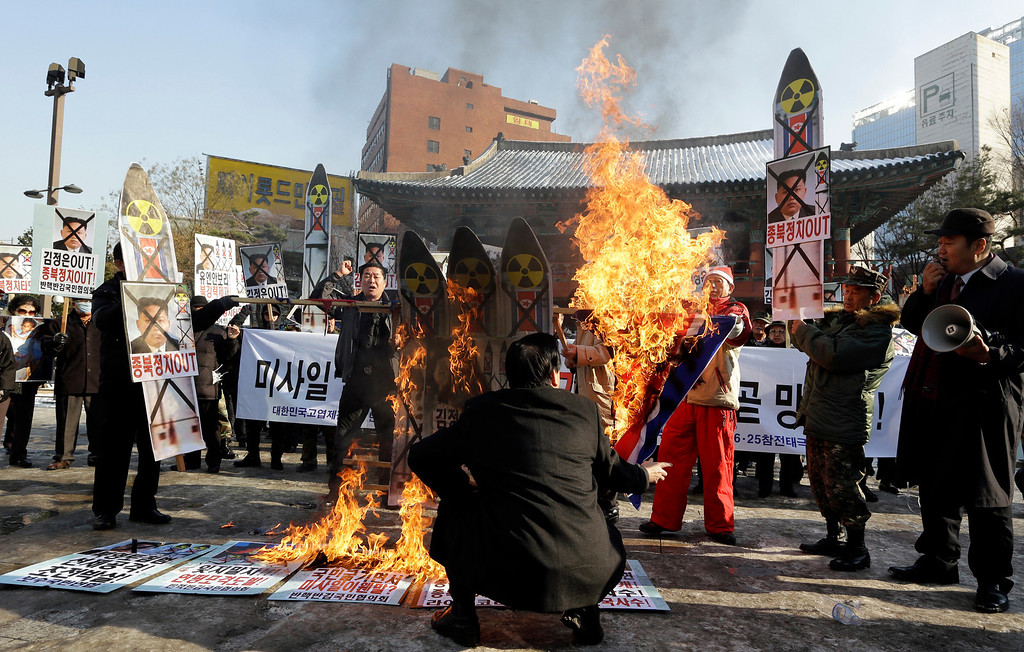 Description of . South Korean protesters burn the pictures of North Korean leader Kim Jong Un, North Korea flags and mock missiles during a rally denouncing North Korea's rocket launch in Seoul, South Korea, Wednesday, Dec. 12, 2012. North Korea successfully fired a long-range rocket on Wednesday, defying international warnings as the regime of Kim Jong Un took a giant step forward in its quest to develop the technology to deliver a nuclear warhead. (AP Photo/Lee Jin-man)