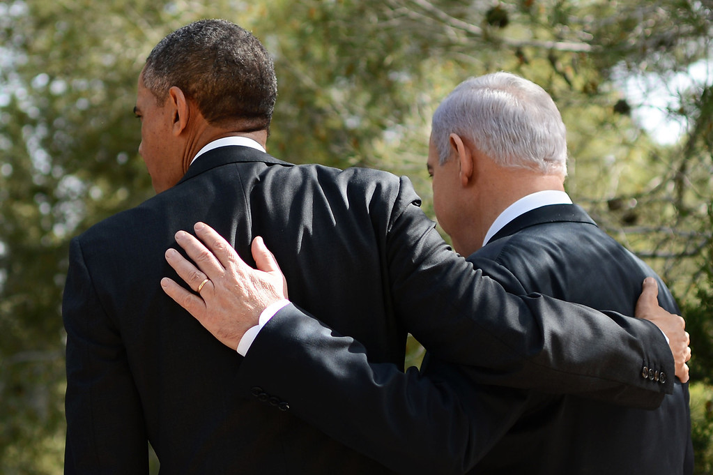 Description of . In this handout photograph supplied by the Government Press Office of Israel (GPO), U.S. President Barack Obama and Israel's Prime Minister Benjamin Netanyahu place their arms around each other during a visit to Yad Vashem at Mount Herzl on March 22, 2013 in Jerusalem, Israel. (Photo by Kobi Gideon/GPO via Getty Images)